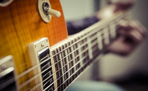 Selective focus photo of a guitarist playing their electric guitar.